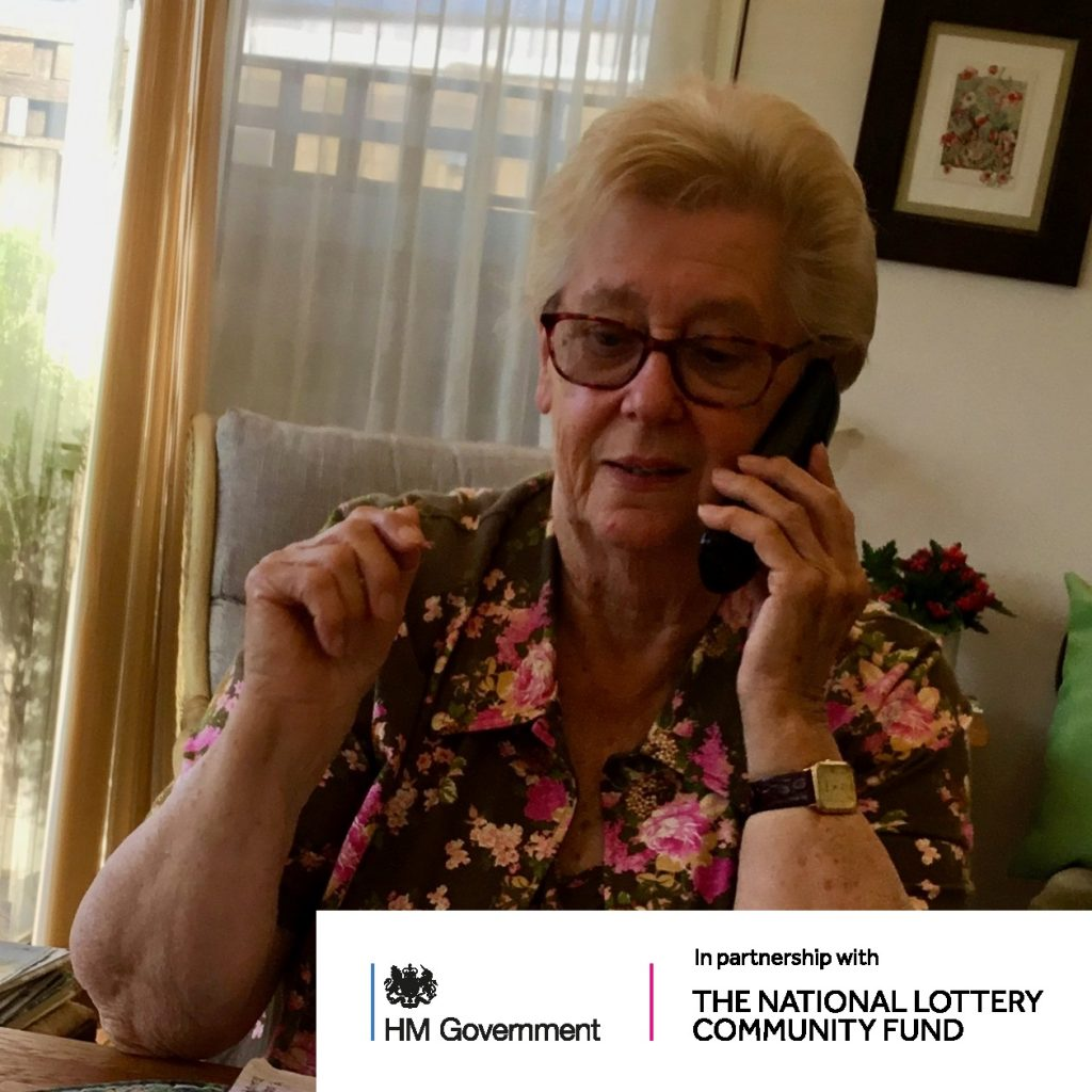 Person on the telephone with National Lottery Funding logo