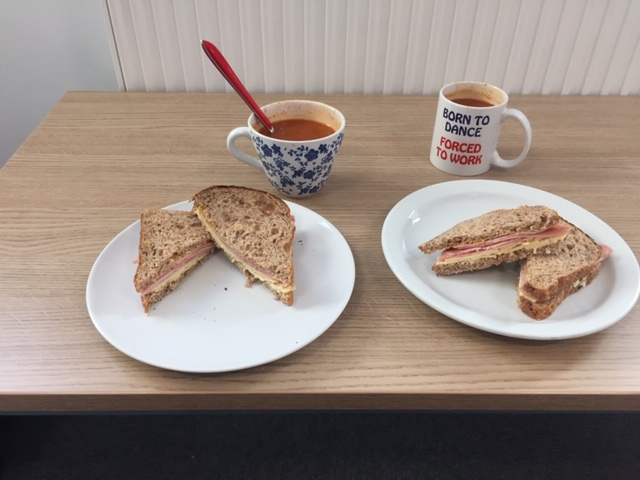 2 plates with sandwiches and cups of tea on a table
