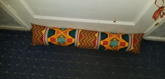 A multi-coloured draft excluder in front of a door